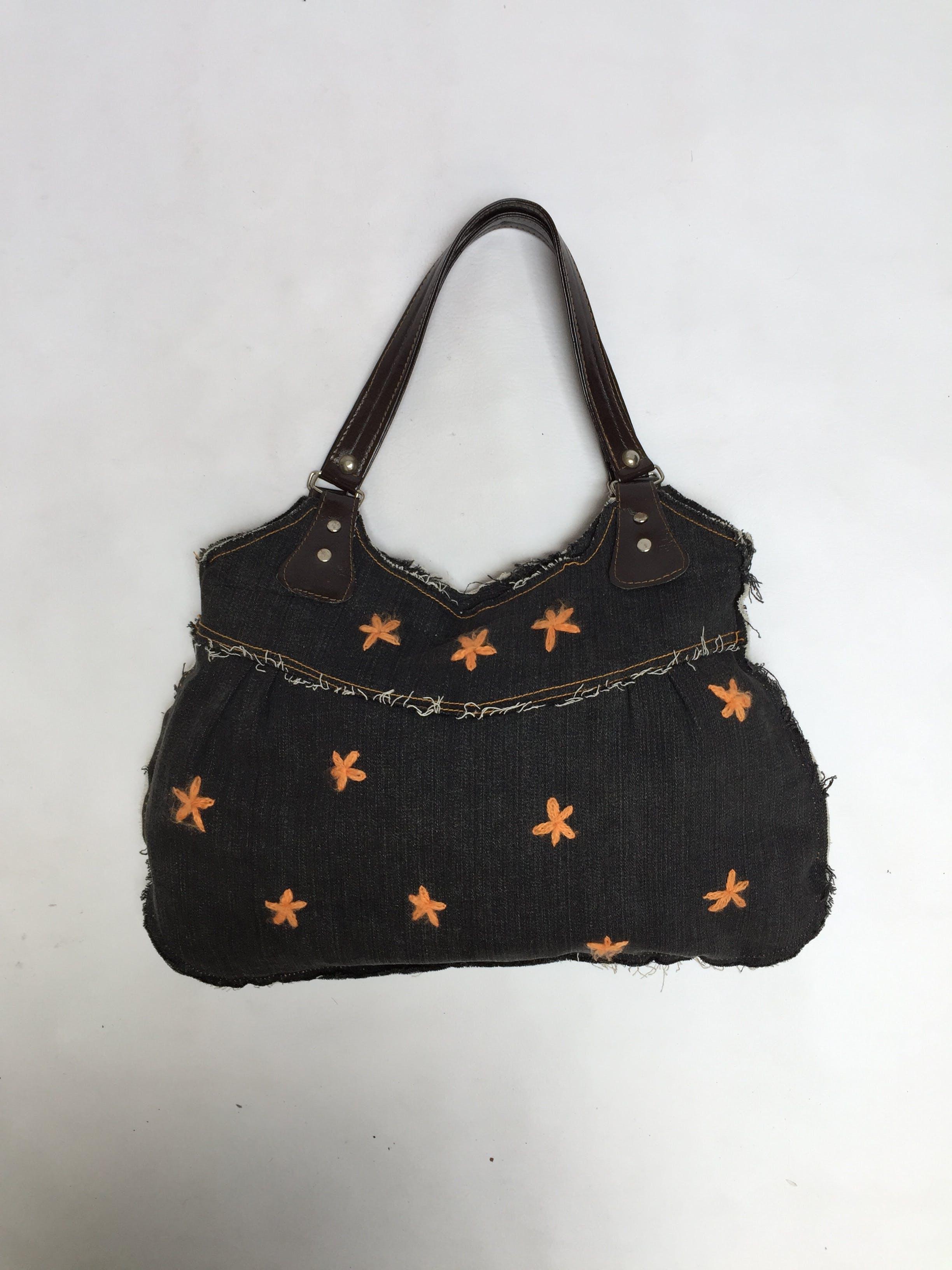 Bolso de jean con flores bordadas en lana naranja y bordes deshilachados, asas marrones y cierre negro, lleva forro. Estado: 9.5/10 Alto: 27 cm Largo: 43 cm